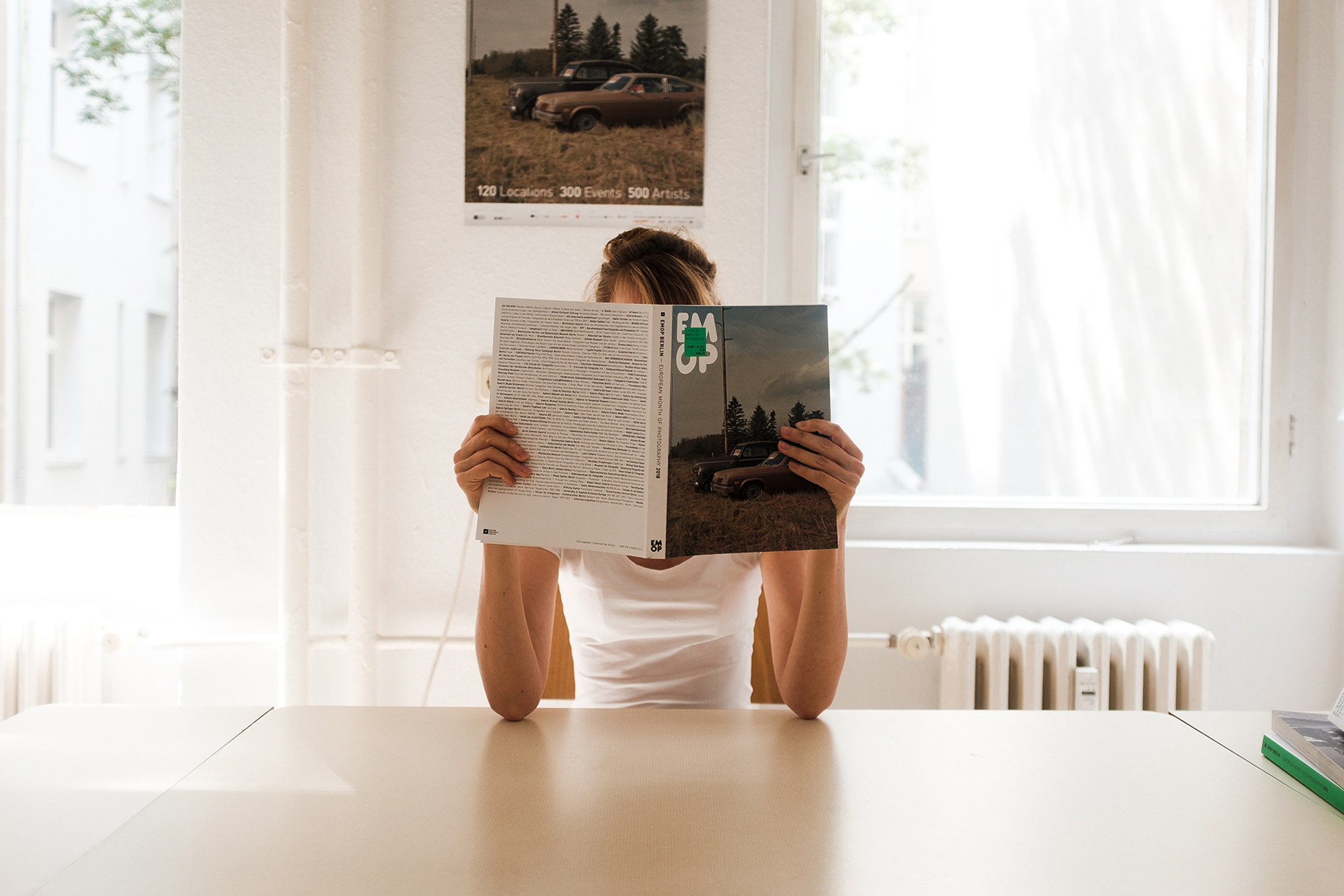 female person sitting inside with book